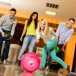 Group of four young smiling people playing bowling — Stockfoto #39147465