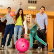Group of four young smiling people playing bowling — Stock Photo #39147493