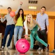 Group of four young smiling people playing bowling — Stock fotografie #39147493