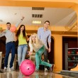Group of four young smiling people playing bowling — Foto de stock #39147501