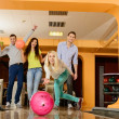 Group of four young smiling people playing bowling — Stock Photo #39147501