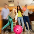 Group of four young smiling people playing bowling — Stock Photo #39147503