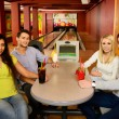 Stock Photo: Group of four young smiling people chatting behind table in bowling club