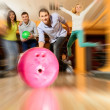 Group of four young smiling people playing bowling — Stockfoto #39147551