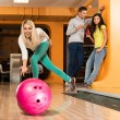 Cheerful young blond woman playing bowling — Stock Photo #39147571