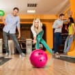 Group of four young smiling people playing bowling — Stockfoto #39147575