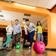 Group of four young smiling people playing bowling — Stockfoto #39147611