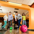 Group of four young smiling people playing bowling — Stock Photo #39147611