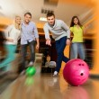 Foto Stock: Group of four young smiling people playing bowling