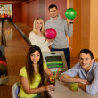 Four young people in bowling club with balls and drinks — Stock fotografie #39147667