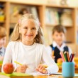 Little schoolgirl sitting behind school desk during lesson in school — Stock Photo