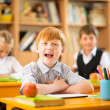 Little redhead schoolboy behind school desk during lesson — Stock Photo #39147863