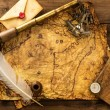 Stock Photo: Sextant, spyglass and envelope on vintage map over wooden background