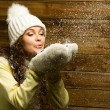 Beautiful woman in knit hat blowing snow from her hands — Stock Photo #39148117