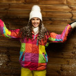Smiling woman in ski jacket and white hat standing against wooden house wall under snow — Stock Photo #39148119