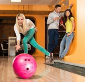 Cheerful young blond woman playing bowling — Stock Photo