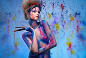 Young woman muse with creative body art and hairdo holding paint brushes — Stock Photo