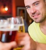 Handsome young man toasting with beer in a pub — 图库照片