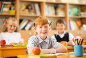 Little redhead schoolboy behind school desk during lesson — Stockfoto