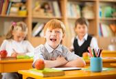 Little redhead schoolboy behind school desk during lesson — Stock Photo