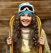 Smiling woman with skies standing against wooden house wall under snow — Stock Photo