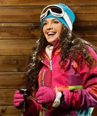 Smiling woman with ski poles standing against wooden house wall — Stock Photo