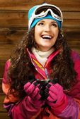 Happy woman in ski wear with cup of a hot drink against wooden wall — Stock Photo