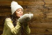 Beautiful woman in knit hat blowing snow from her hands — Stock Photo