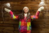 Smiling woman in ski jacket and white hat standing against wooden house wall under snow — Stock Photo