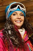 Smiling woman in ski jacket and ski mask against wooden house wall — Stock Photo
