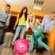 Group of four young smiling people playing bowling — Stock Photo #39601657