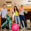 Group of four young smiling people playing bowling — Stockfoto #39601667
