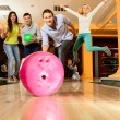 Group of four young smiling people playing bowling — Stock Photo #39601699