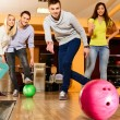 Group of four young smiling people playing bowling — Foto de stock #39601753