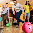 Group of four young smiling people playing bowling — Stock Photo #39601753