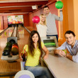 Foto Stock: Four young people in bowling club with balls and drinks