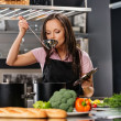 Cheerful young woman in apron on modern kitchen with ladle tasting from pot — Stock Photo