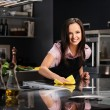 Young cheerful woman cleaning modern kitchen — Stock Photo
