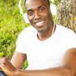 Young african american man in white shirt listens music in a park — Stock Photo #39601957