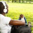 Young african american man in white shirt listens music in a park — Stock Photo #39601959