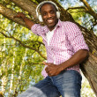 Positive young african american man listens music in a park — Stock Photo #39602035