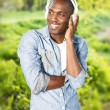 Positive young african american man listens music in a park — Stock Photo #39602043