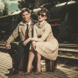 Beautiful vintage style couple sitting on suitcases on train station platform — Stock Photo