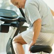 Senior man adjusting seat on a bike machine in a fitness club — Stock Photo