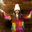 Smiling woman in ski jacket and white hat standing against wooden house wall under snow — Stock Photo #39602703