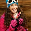 Happy womin ski wear with cup of hot drink against wooden wall — Stock Photo #39602705