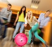 Group of four young smiling people playing bowling — Stock fotografie