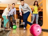 Group of four young smiling people playing bowling — Stock Photo