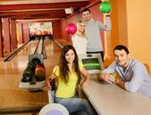 Four young people in bowling club with balls and drinks — Stock Photo