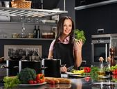 Happy young woman in apron on modern kitchen cutting vegetables — Stock Photo